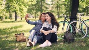 俏丽的女朋友在公园采取selfie坐有自行车的草坪在背景中 混合的族种友谊 股票视频