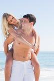 给他俏丽的女朋友肩扛的愉快的人 免版税图库摄影