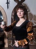 俏丽的妇女一把扶手椅子和有酒杯的 免版税库存照片