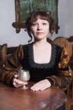 俏丽的妇女一把扶手椅子和有酒杯的 免版税库存图片