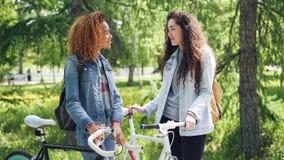 俏丽的妇女与她站立在公园在晴朗的夏日,女孩的非裔美国人的朋友骑自行车者谈话聊天 影视素材