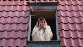 俏丽的妇女从有双重斜坡屋顶的房屋的房子窗口看并且喝咖啡 影视素材