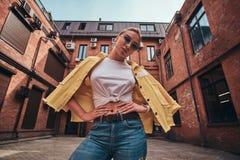 俏丽的妇女低角度照片太阳镜和牛仔布的在相称围场 免版税库存照片