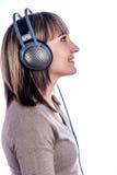 俏丽的妇女听的音乐 图库摄影