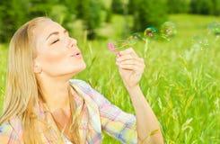 俏丽的妇女吹的肥皂泡在公园 免版税图库摄影