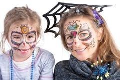俏丽的妇女和她的女儿万圣夜构成的 免版税库存图片