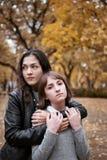 俏丽的妇女和青少年的女孩画象  他们在秋天公园摆在 在秋季的美好的风景 图库摄影