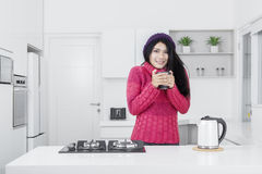 俏丽的妇女在厨房里拿着热的饮料 库存图片