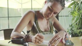 俏丽的妇女在学报,日志书写 咖啡杯表 股票录像