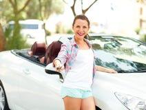 年轻俏丽的妇女在有的敞篷车汽车附近站立 图库摄影