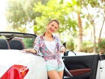 年轻俏丽的妇女在有的敞篷车汽车附近站立 免版税库存图片