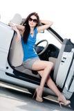 俏丽的妇女在有被打开的边门的白色汽车坐 免版税库存图片
