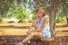 俏丽的妇女在橄榄色的庭院里 图库摄影