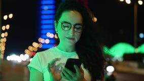俏丽的妇女在白色T恤的街道上站立,并且玻璃,由信用卡和智能手机付网上付款 股票视频
