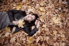 俏丽的妇女在落叶的秋天公园在 在秋季的美好的风景 免版税库存图片