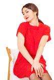 俏丽的妇女坐一把椅子用她的手 免版税图库摄影