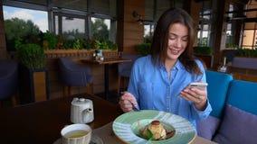 俏丽的妇女坐在咖啡馆,聊天由智能手机和饮用点心在慢动作 股票录像