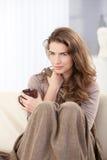 俏丽的妇女坐沙发饮用的茶 免版税库存照片