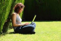俏丽的妇女坐草在有膝上型计算机的一个公园 库存照片