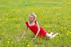 俏丽的妇女坐草甸 免版税库存图片