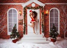 俏丽的妇女室外在圣诞老人红色衣裳  图库摄影