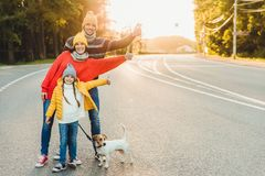 俏丽的妇女室外画象,她的丈夫和女儿显示好标志,走与在路的狗,享受阳光,有活跃lifest 免版税图库摄影