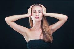 俏丽的妇女对负顶头在站立反对黑backgr的手上 免版税图库摄影