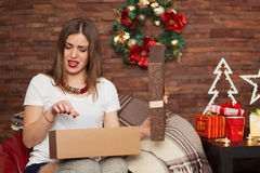 俏丽的妇女开头圣诞节礼物 免版税库存照片
