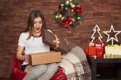 俏丽的妇女开头圣诞节礼物 免版税库存图片
