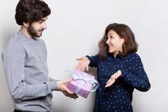 年轻俏丽的妇女惊奇从她的男朋友接受礼物 站立在白色墙壁附近的年轻美好的夫妇 博若莱红葡萄酒 免版税库存图片