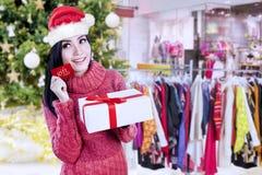 俏丽的妇女拿着礼品券在购物中心 免版税库存照片