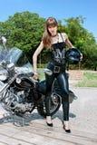 俏丽的妇女暂挂黑色摩托车盔甲 图库摄影