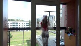 年轻俏丽的妇女浪花化学制品和抹窗口在客户回家 股票视频