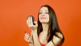 俏丽的妇女演播室画象红顶的使用明亮的唇膏和拿着一点镜子手中在橙色背景 影视素材
