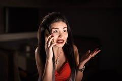 俏丽的妇女红色礼服的和有长的头发的谈话在电话 图库摄影