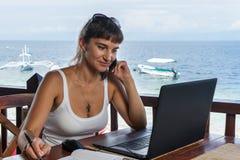 年轻俏丽的妇女自由职业者作家与膝上型计算机笔记薄和电话一起使用在蓝色热带海前面 免版税库存照片