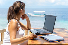 年轻俏丽的妇女自由职业者作家与膝上型计算机蓝色热带海一起使用笔记薄和电话infront  免版税库存图片