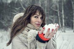 年轻俏丽的妇女获得乐趣在有雪的冬天森林在手上 免版税库存照片