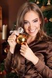 俏丽的妇女装饰圣诞树 免版税库存图片
