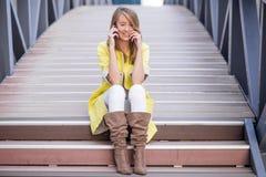年轻俏丽的妇女谈话在桥梁的手机-妇女有交谈在智能手机 免版税库存图片