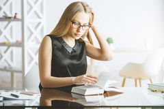 俏丽的妇女阅读书在办公室 库存图片