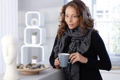 俏丽的妇女饮用的咖啡在家 图库摄影