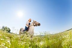 俏丽的妇女骑马术在用花装饰的草甸 图库摄影