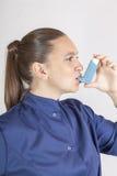 俏丽的妇女,护士,使用哮喘吸入器 免版税库存图片