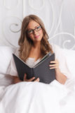 俏丽的妇女读书在床上 图库摄影