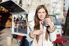 年轻俏丽的妇女画象有一个杯子的在晴朗的户外背景的热的饮料 免版税库存图片