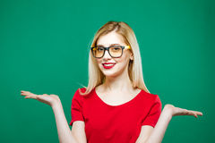 年轻俏丽的妇女画象有长的拿着在她的两只手上的金发、镜片和红顶的空的空间  免版税库存照片