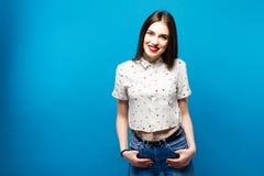 年轻俏丽的妇女smilig和身分确信的蓝色背景 免版税库存照片