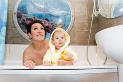 俏丽的妈妈和逗人喜爱的婴孩在卫生间里 图库摄影