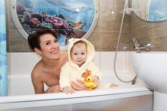 俏丽的妈妈和逗人喜爱的婴孩在卫生间里 免版税库存图片